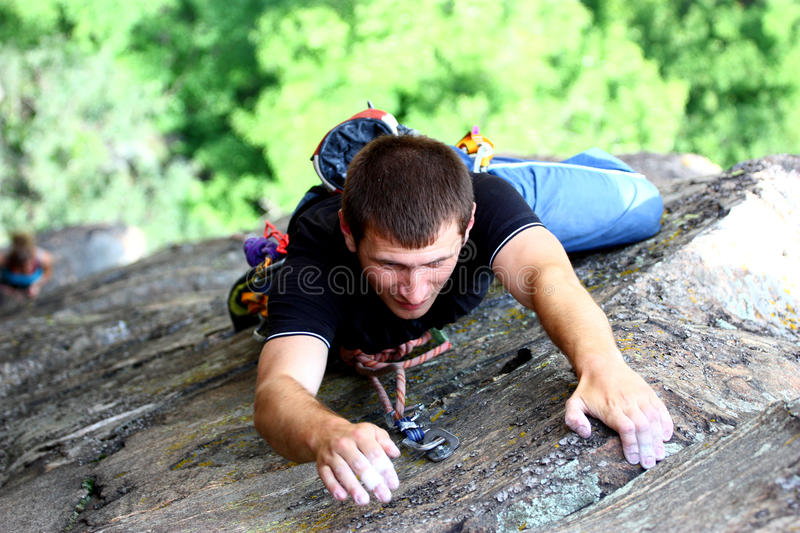 Extreme claiming. A climber extreme claiming stone wall outdoor reaching for the summit royalty free stock photos