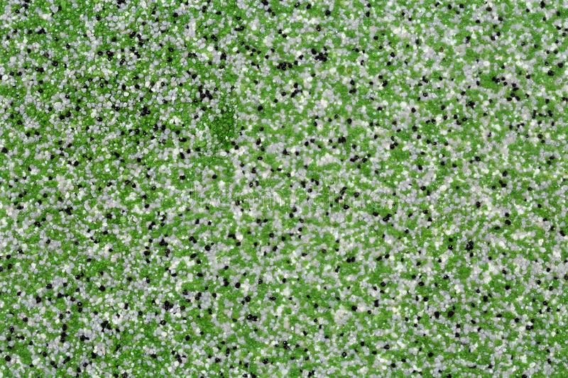 Extreme close up of decorative quartz sand epoxy floor or wall coating with green, grey, white and black coloured particles royalty free stock photos