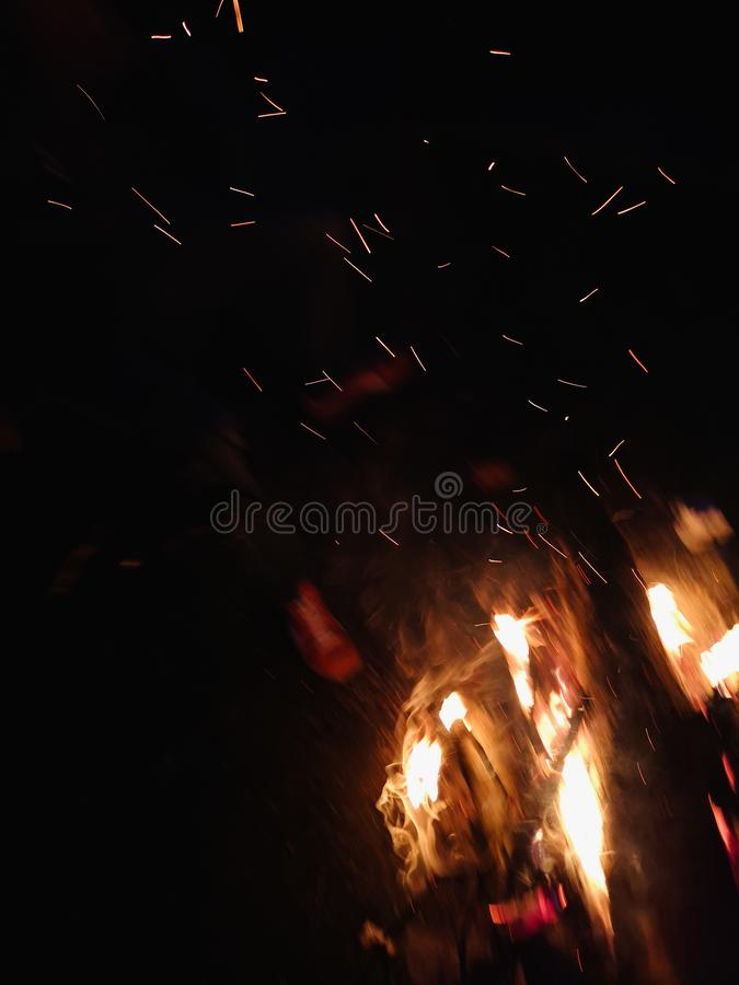 Extreme close up of fire sparks moving on dark night sky as black background coming from brightly burning warm outdoors stock images