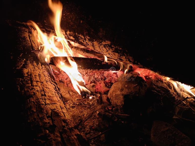 Extreme close up of fire sparks moving on dark night sky as black background coming from brightly burning warm outdoors stock photography