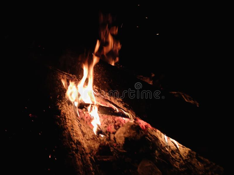 Extreme close up of fire sparks moving on dark night sky as black background coming from brightly burning warm outdoors stock photo