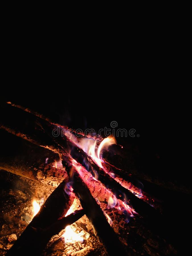 Extreme close up of fire sparks moving on dark night sky as black background coming from brightly burning warm outdoors royalty free stock photo