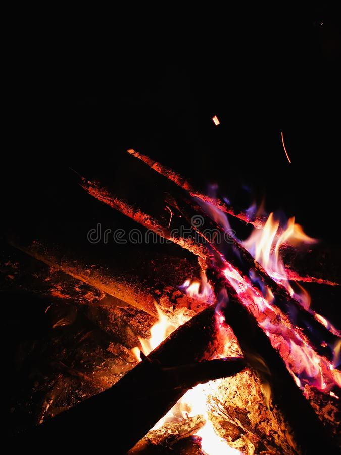 Extreme close up of fire sparks moving on dark night sky as black background coming from brightly burning warm outdoors stock photos