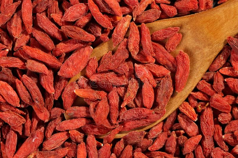 Extreme close up, flat lay of dried goji berries with wooden spoon. Macro food background texture royalty free stock photo