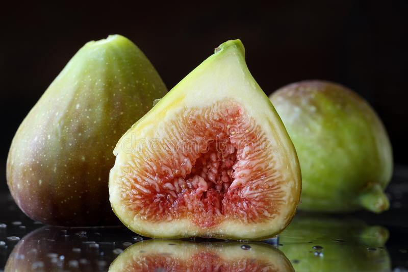 Extreme close up of the inside of a fig. Two and a half sliced fresh fig fruits on a black background with reflections and water d stock photo
