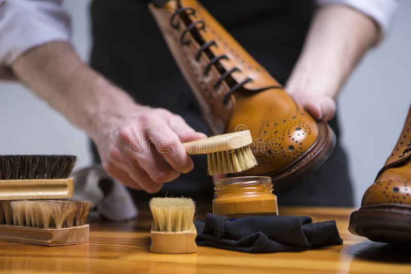 Extreme Close Up of Mans Hands Cleaning Luxury Calf Leather Brogues with Special Accessories And Tools. stock photo