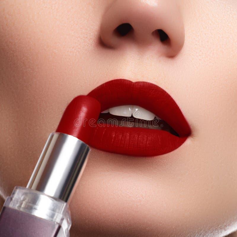 Extreme close up on model applying dark red lipstick. Makeup. Professional fashion retro make-up. dark red lipstick. Wine Lips stock photography