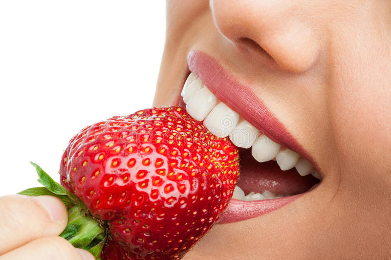 Extreme close up of teeth biting strawberry. stock images
