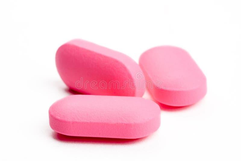 Extreme close-up van roze pillen die op wit worden geïsoleerd¯ stock afbeelding