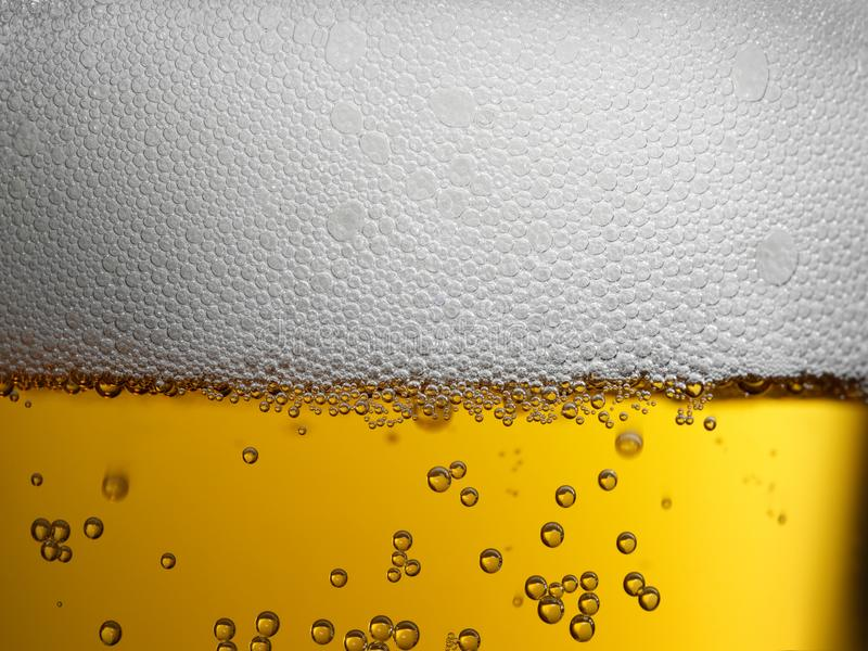 Extreme closeup of gold amber beer with frothy head and bubbles. Closeup of freshly poured gold amber beer with frothy head and carbonation bubbles stock images