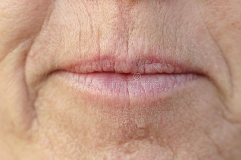 Extreme Closeup on the mouth of a middle-aged woman. Extreme Closeup on the mouth of a middle-aged brunette woman with her mouth closed and a serious expression royalty free stock photo