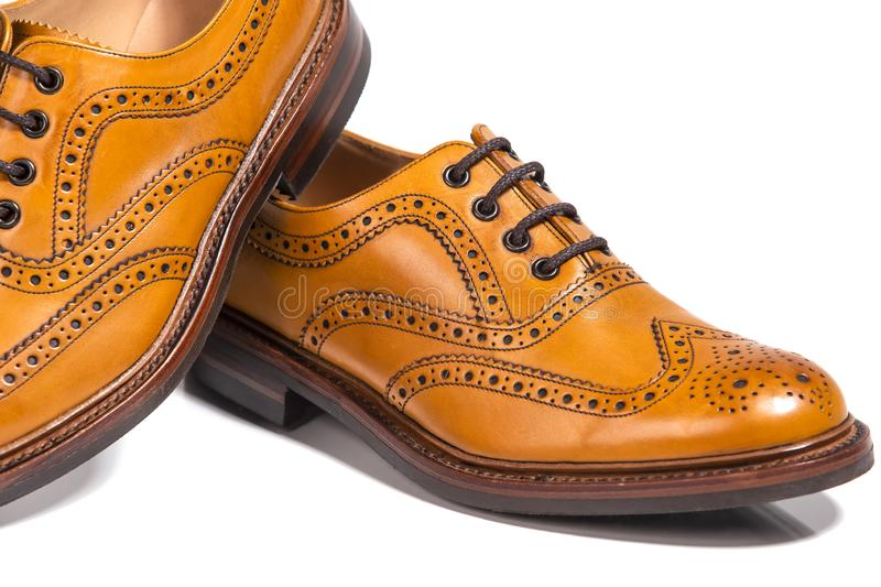 Extreme Closeup of A Pair of Full Broggued Tan Leather Oxfords Shoes. Concepts of Luxury Male Footwear. Extreme Closeup of A Pair of Full Broggued Tan Leather stock photo