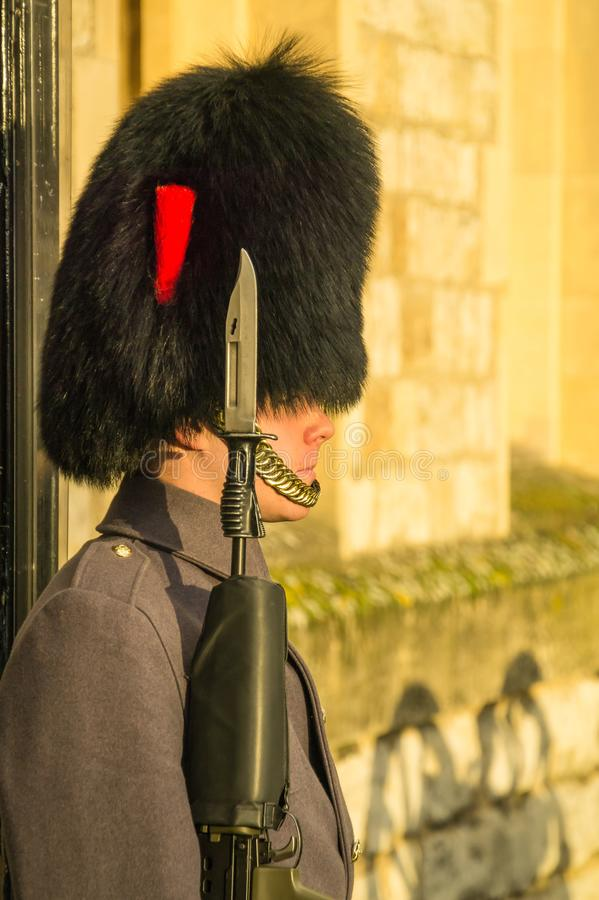 Extreme closeup of sentry at Tower of London in modern uniform. Showing detail of his bearskin hat and gun with bayonet royalty free stock images