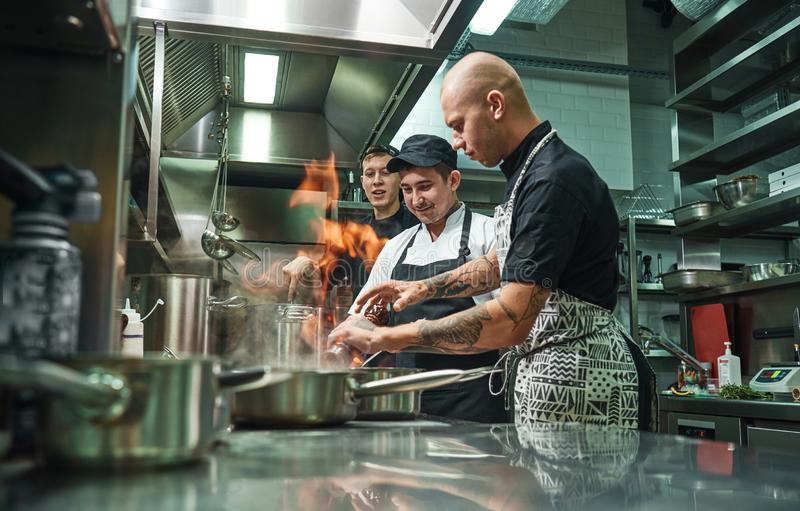Extreme cooking. Profesional chef teaching his two young trainees how how to flambe food safely. Restaurant kitchen stock image