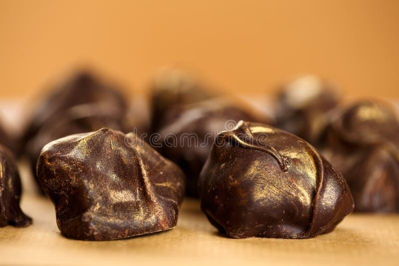 Extreme dichte omhooggaand van verse, heerlijke en gezonde eigengemaakte ruwe chocoladebonbons met gouden bestrooit op beige acht stock afbeeldingen