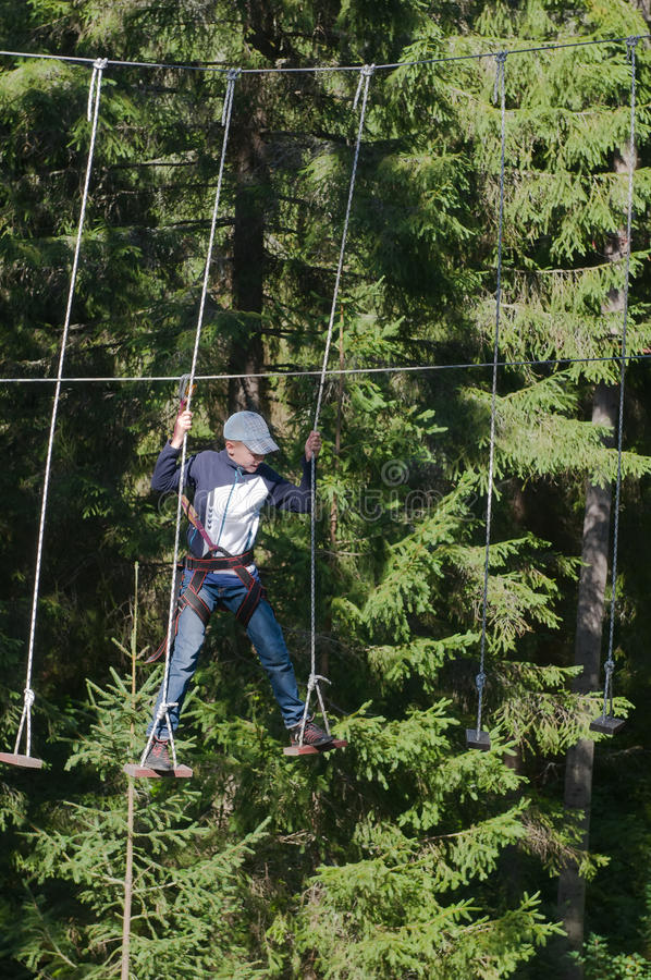 Extreme exercise at altitude. The boy moves at a height on the ropes royalty free stock photography