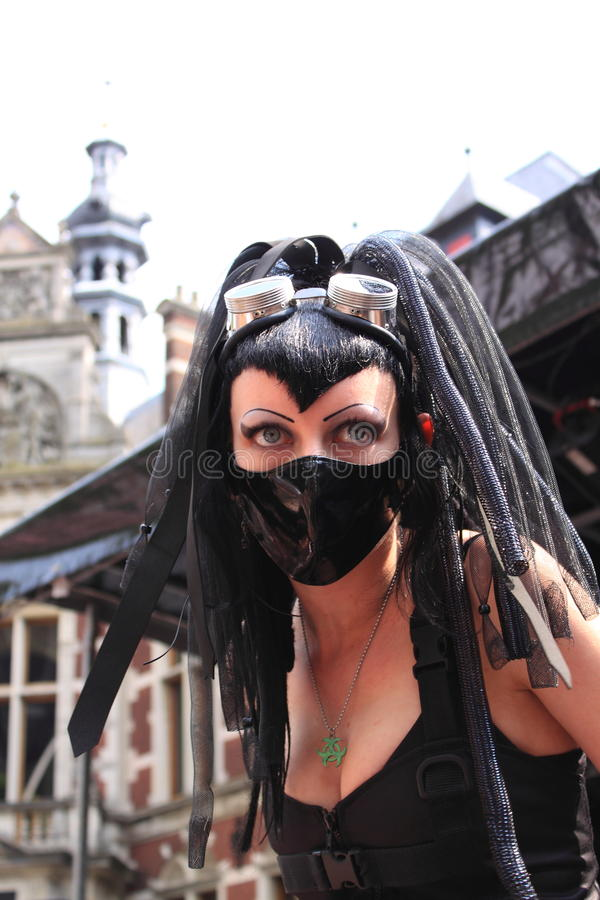 Extreme gothic fashion show. Gothic woman wearing black leather clothes and face mask on the catwalk during the gothic festival summer darkness in the city royalty free stock image