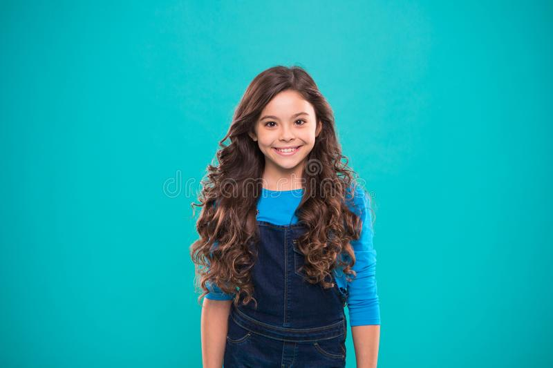 Extreme hair volume. Kid girl long healthy shiny hair. Kid happy cute face with adorable curly hairstyle stand over blue. Background. Little girl grow long hair stock photos
