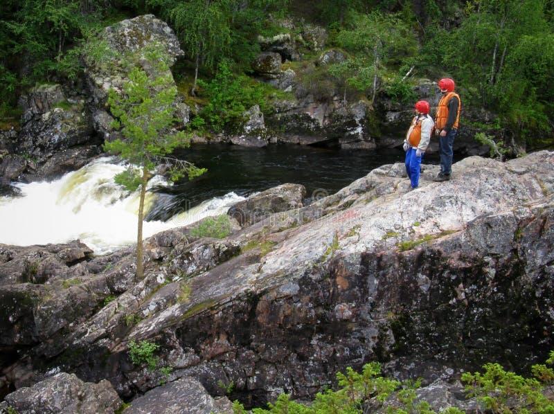 Extreme. KOLA PENINSULA, RUSSIA - AUGUST 11 - Men in the life vest examines threshold mountain river in Kola Peninsula on August 11, 2008 stock image