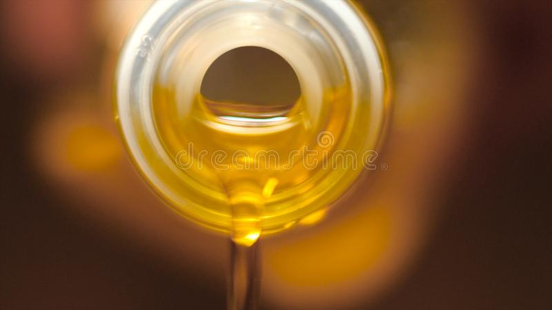 Extreme macro of olive oil poured from an original bottle. Stock footage. Close-up of oil pouring out of the bottle royalty free stock photos
