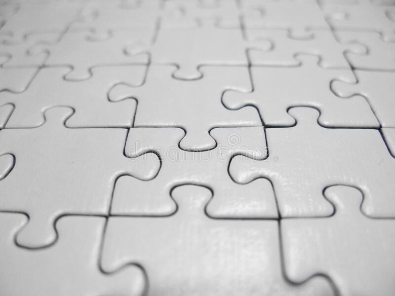 Extreme macro of white puzzle pieces stock photography