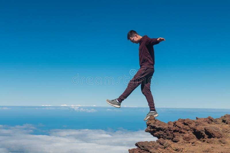 Extreme mens die en zich op de hoge rand van de bergklip bevinden in evenwicht brengen stock foto's