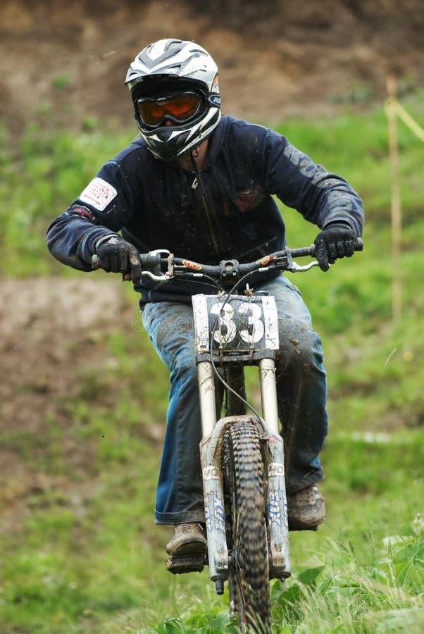 Extreme mountain bike downhill contest under rain royalty free stock photo