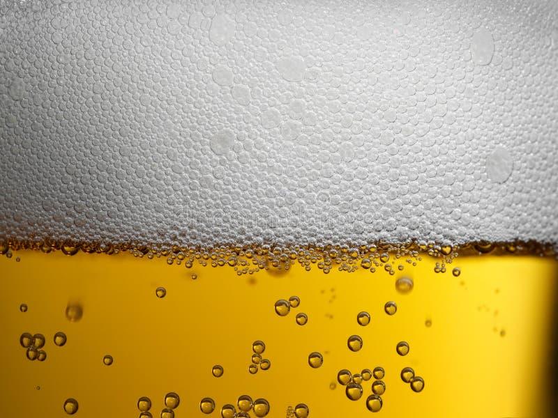 Extreme Nahaufnahme des Goldbernsteinfarbigen Bieres mit schaumigem Kopf und Blasen stockbilder
