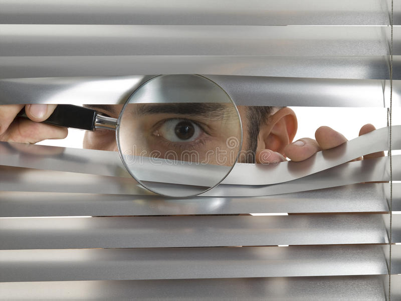 Extreme peeping Tom. A man is peeping through the blinds with a magnifying glass royalty free stock images