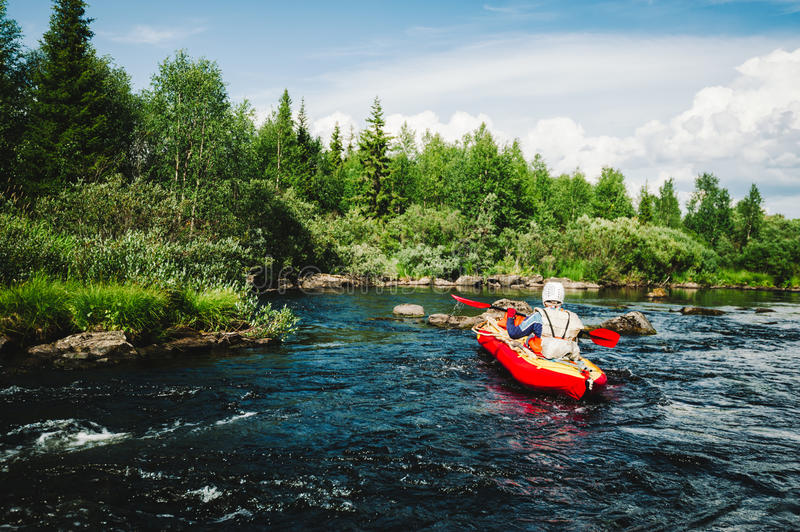 Extreme rafting. On the rapid river on an inflatable red kayak stock photography