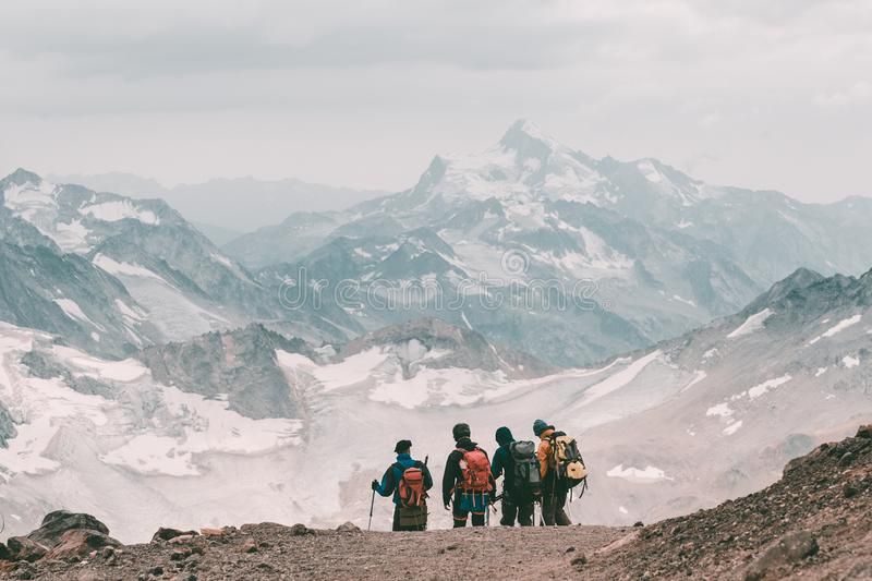 Extreme recreation and mountain tourism. A group of hikers down the mountain path over the horizon. In the background, large snow-. Capped mountains. Copy space stock images
