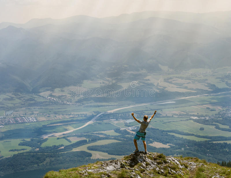 Extreme runner finally climbs the mountain top and see wide valley royalty free stock photography