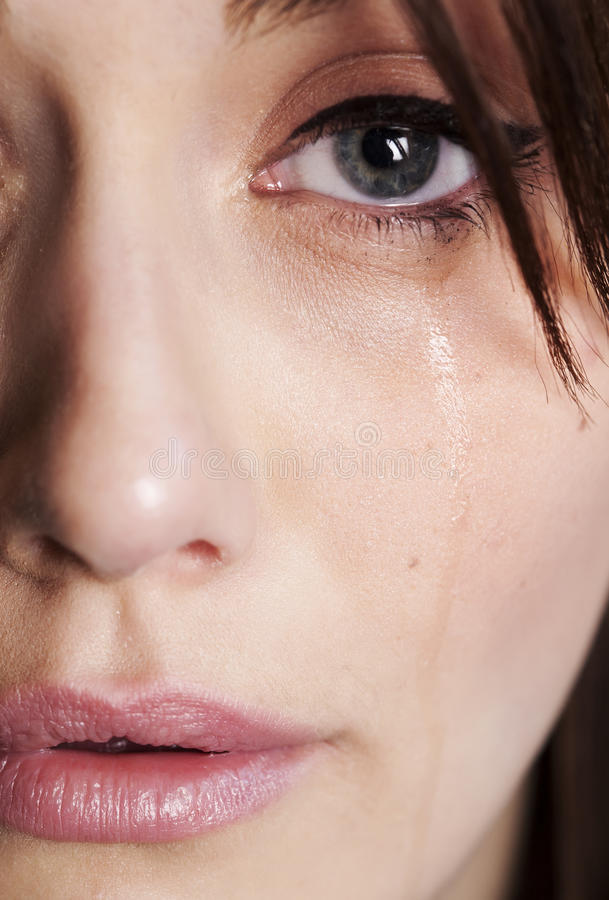 Extreme Sadness. A tight close up of half of a womans face with tear running down cheek from crying stock photos