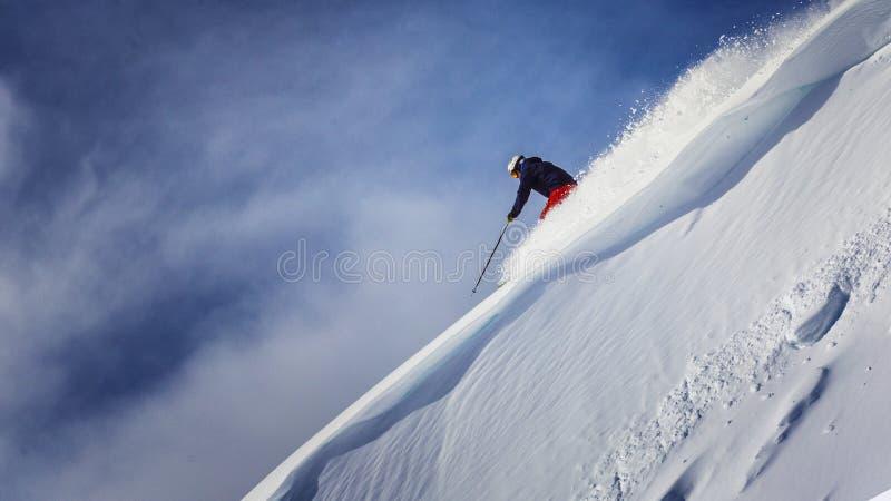 Extreme skiër die onderaan steile helling laden stock afbeeldingen