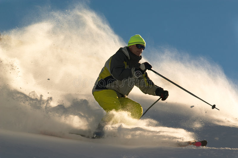 Extreme skier. Man on ski tear at full speed in cluods of snow powder stock images
