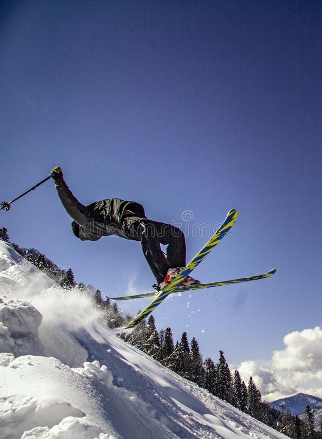 Extreme skier doing flips. In the air going down the mountain royalty free stock images