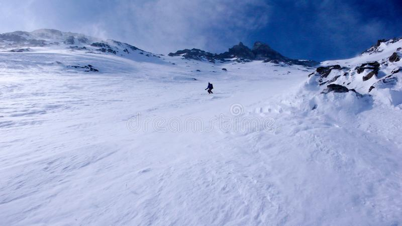 Extreme skier on a very steep north face of a high alpine mountain peak stock photography