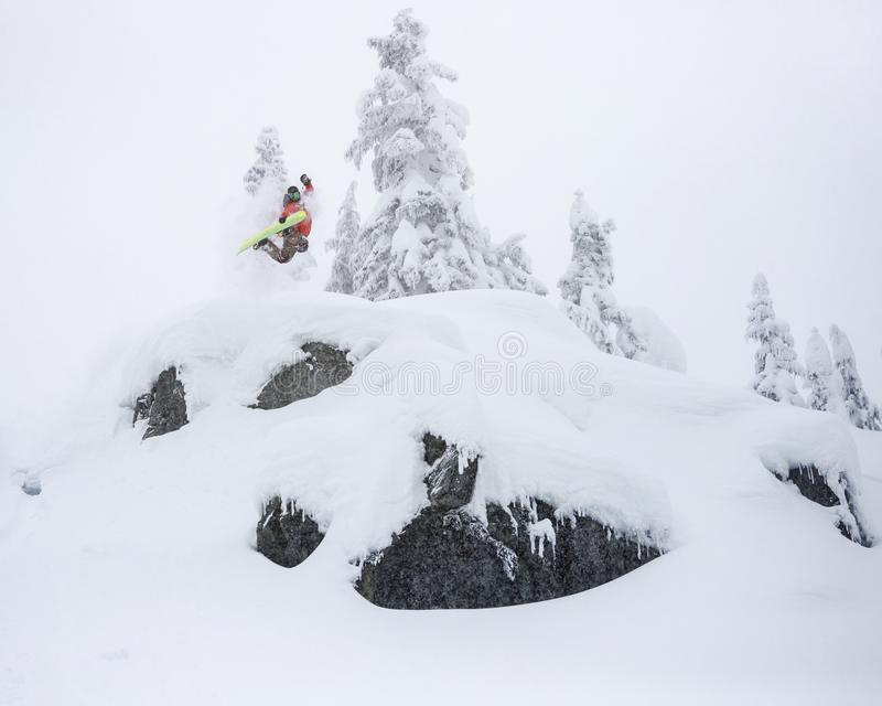 Extreme Snowboarder Jumping Off Powder Cliff Holding Grab in Backcountry stock photo