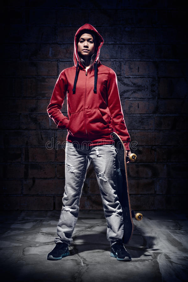 Extreme sport. Skateboarder portrait extreme sport skater with grunge wall and red hoodie royalty free stock images
