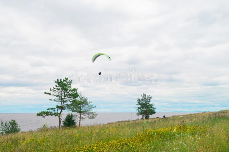 Extreme sport. paraglider in the sky over the open sea against the blue sky, white clouds of green grass and trees on a cloudy day. Landscape royalty free stock images