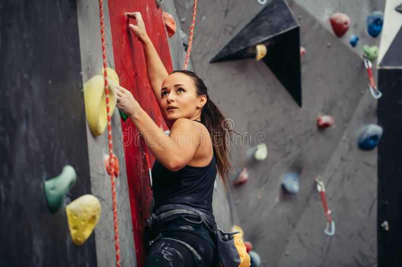 Extreme sport, stress relief, bouldering, people and healthy lifestyle concept. Young sporty muscular woman climbing up on top of rock wall in gym, side view royalty free stock photos