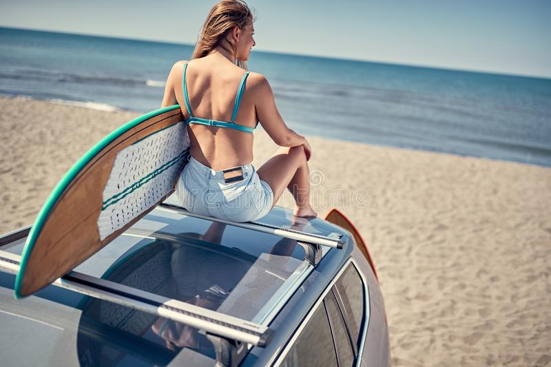 Extreme Sport. Surfing. surfer girl sitting on the car and getting ready for surfing. stock photography