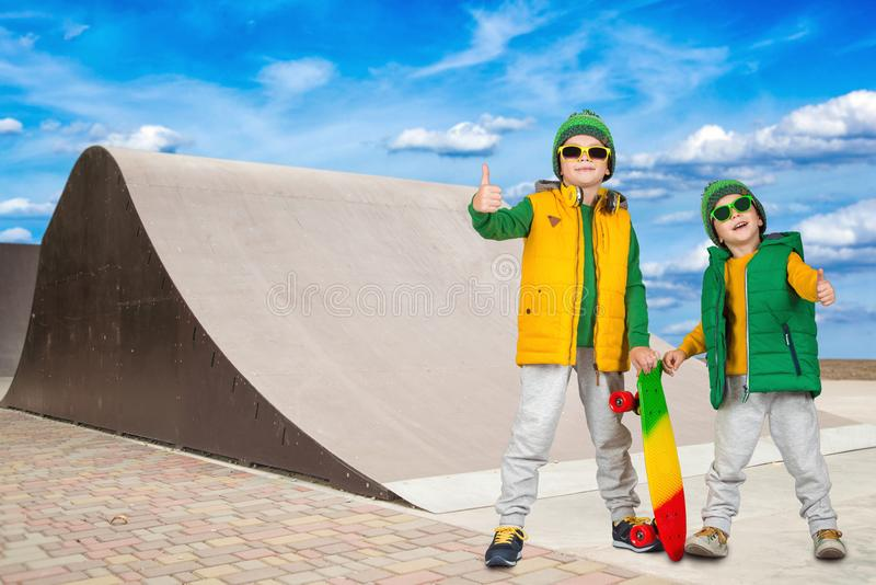 Two brothers riding on steep hills to skateboard at the skate Park.Extreme sports. royalty free stock photos