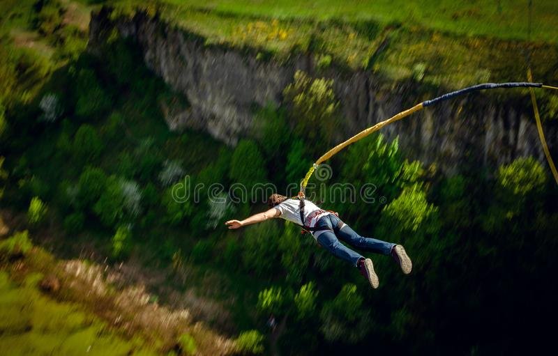 An extreme sportsman jumps on a rope from a great height. stock images