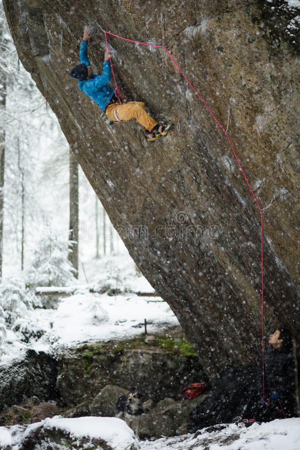 Extreme winter sport. Rock climber ascending a challenging cliff. Extreme sport climbing. Freedom, risk, challenge, success. stock image