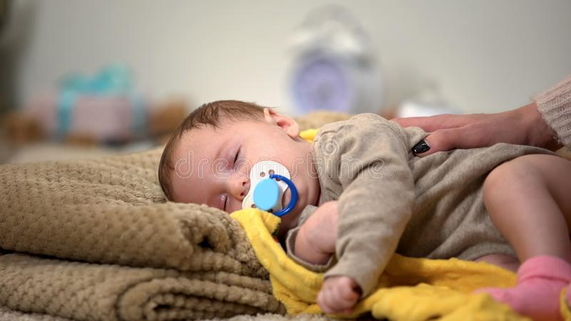 Extremely cute newborn baby sleeping sucking binky, healthy child development stock photography