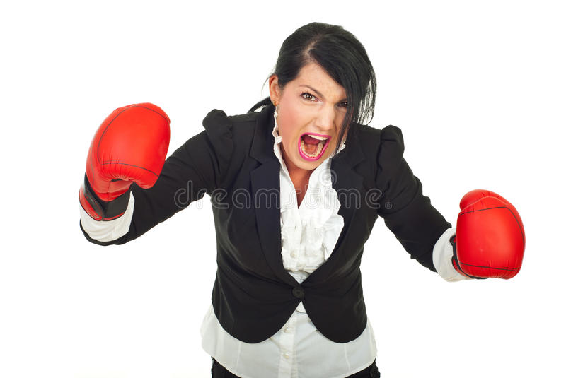 Extremely furious businesswoman in attack. Extremely furious business woman in attack with boxing gloves against white background stock photography