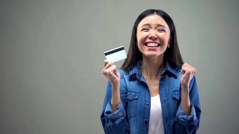 Extremely happy asian woman holding credit card, low interest rate for crediting royalty free stock image