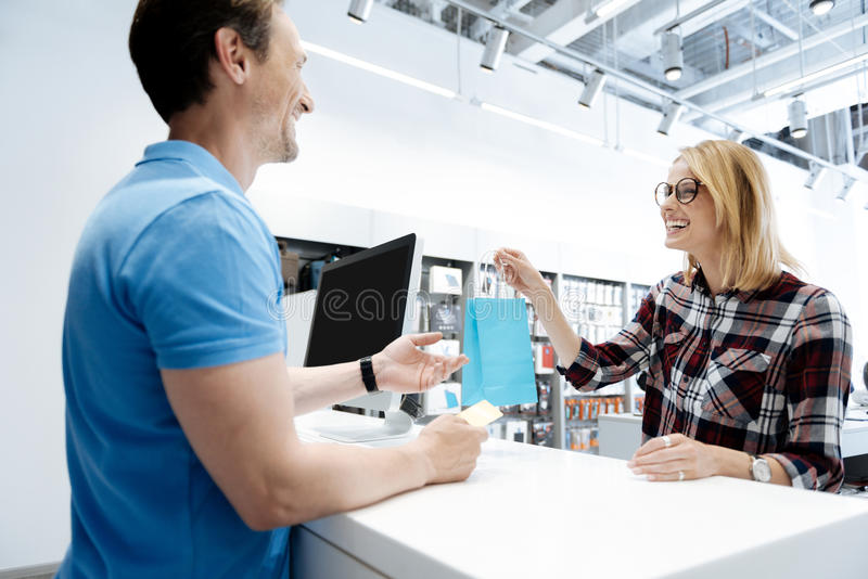 Extremely happy young lady making purchases at electronics store. Thank you for purchasing with us. Excited female shopper cannot keep her emotions inside while royalty free stock image