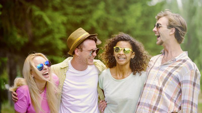 Extremely happy young people laughing at joke, close friends meeting outdoors royalty free stock photography